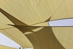 Canvas canopy overhead. Light brown canvas canopy against a light blue sky stock photo