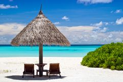 Canvas chairs with parasol. On a beautiful beach Stock Photo