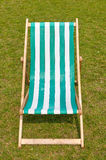 Canvas deckchair on a grassy lawn in the summer. Canvas green striped deckchair on a grassy lawn in the summer Royalty Free Stock Photos