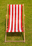 Canvas deckchair on a grassy lawn in the summer. Canvas red striped deckchair on a grassy lawn in the summer Royalty Free Stock Photo