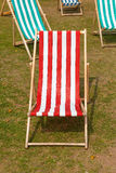 Canvas deckchairs on a grassy lawn in the summer. Stock Photo