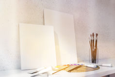 Canvas and drawing tools toning. Two blank canvas, oil paint palette and brushes on white desktop and concrete wall background. Toned image. Mock up, 3D Stock Photos