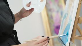 Canvas, an easel and a brush for drawing: close-up, only hands. The process of drawing with a brush on the canvas: the female hands hold the brush and draw with stock video footage