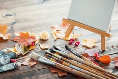 Canvas on easel, paint tubes, brushes and autumn leaves on desk. Stock Photos