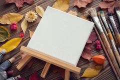 Canvas on easel, paint tubes, brushes for painting and autumn leaves on desk. Royalty Free Stock Photography
