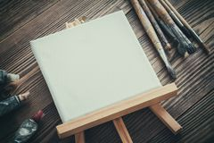 Canvas on easel, paint tubes and brushes on wooden desk. Stock Photo