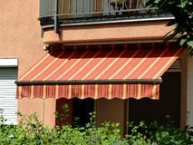 Canvas fabric awning sunshade in yellow & orange over a balcony