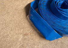 Canvas hose rolled on the concrete floor Royalty Free Stock Images