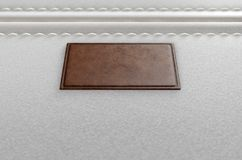 Canvas Material And Leather Label. A close up view of a section of white canvas fabric with a blank tan leather label stitched onto it - 3D render Stock Images