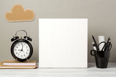 Canvas mock up on table. Blank canvas mock up with pencil and alarm clock. Modern stylish interior background for social media and marketing Royalty Free Stock Photo