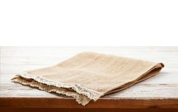 Canvas napkin with lace, tablecloth on wooden table on white background. Can used for display or montage your products. Empty canvas napkin with lace, tablecloth stock image