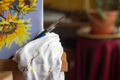Canvas, paint, brushes, palette knife lying on the table. Stock Image