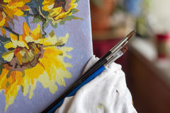 Canvas, paint, brushes, palette knife lying on the table. Royalty Free Stock Photos