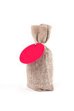 Canvas sack with blank label. Canvas sack with blank red label isolated on white Royalty Free Stock Images