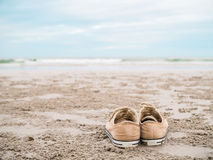 Canvas shoes on the beach. Yellow canvas shoes on the beach - fashion accessory Royalty Free Stock Image