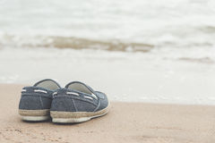 Canvas shoes on sand beach. With copy space on right,vintage filter Royalty Free Stock Photos