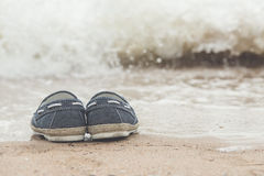 Canvas shoes on sand beach. With copy space on right,vintage filter Royalty Free Stock Images
