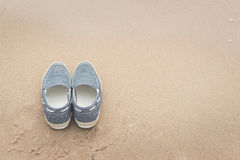 Canvas shoes on sand beach. With copy space on right,vintage filter Stock Photo