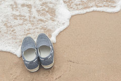 Canvas shoes on sand beach. With copy space on right,vintage filter Royalty Free Stock Image