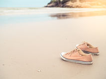 Canvas shoes on the sand beach. Yellow canvas shoes on the sand beach in vintage filter tone and light effect Stock Image