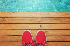 Canvas shoes on wooden deck. View from above Stock Photos
