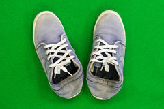 Canvas sneakers Placed on a green background Royalty Free Stock Image