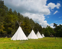 Canvas Teepee, Wigwam. Canvas teepees on a meadow surrounded by forest stock photos