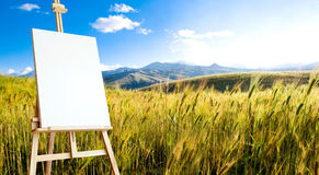 Canvas on tripod on beautiful wheat landcape Royalty Free Stock Photo