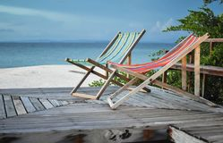 Canvasbed bij houten vloer en strand in blauwe hemel Stock Afbeelding
