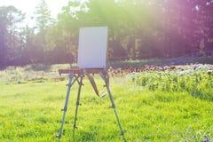 Canvason blanc un chevalet dans un beau jardin botanique dans le r Photos stock