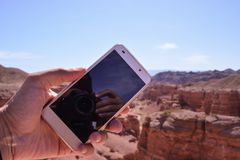 Phone on hand. Charyn canyon. royalty free stock photo