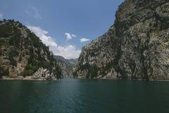 Canyon la chiara acqua nella corrente fra le rocce ed il rovesciamento in un bacino idrico enorme Immagini Stock