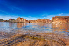 Canyon Lake clear calm waters. The red cliffs surrounding Canyon Lake, reflected in the calm waters on a sunny Winter afternoon Royalty Free Stock Image