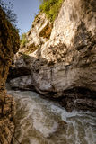 Canyon�and river flowing with foam. Vertical outdoors shot of small fast river streaming with foam and big rocks of Hajokh gorge Stock Photography