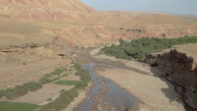Canyon with river stream flowing to Atlas Mountain. Canyon with a river stream flowing to the Atlas Mountain near Ouarzazate city in Morocco stock video footage