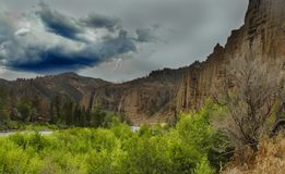 Canyon storm. Dark clouds and lightning over canyon Stock Photos