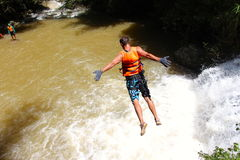 Canyoning male jumping into canyon Vietnam. Waterfall decent jump Stock Photography