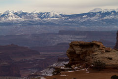 Canyonlands Lookout and Snowy Mountains. A pulled in landscape photo of the diversity in Canyonlands National Park Utah. Sheer drop offs and rises in geological Royalty Free Stock Images