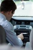 Canzone cambiante dell'uomo in automobile Fotografia Stock