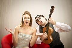 Canzone di amore delle ukulele del gioco del ragazzo dell'uomo del nerd per la sua amica per il giorno di S. Valentino Immagini Stock