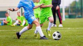 Caçoa o fósforo de futebol Meninos que retrocedem a bola do futebol no campo de esportes Fotos de Stock Royalty Free