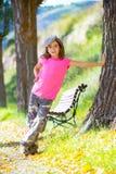 Caçoe a menina com calças e tampão da camuflagem no banco de parque exterior Imagens de Stock