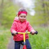 Caçoe a menina que monta sua primeira bicicleta, fora Imagens de Stock