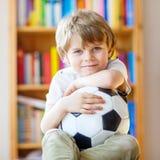 Caçoe o jogo de observação do futebol ou de futebol do menino na tevê Fotos de Stock