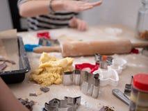 Caos do Natal: Fontes e menina de cozimento que formam a massa da cookie no fundo imagem de stock royalty free