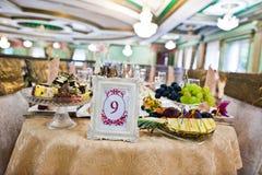 Capítulo con el número nueve en la tabla de huésped en restaurante de la boda Imagen de archivo libre de regalías