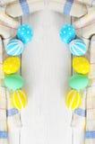 Capítulo con los huevos de Pascua pintados en colores en colores pastel en un fondo blanco Capítulo Imagen de archivo libre de regalías