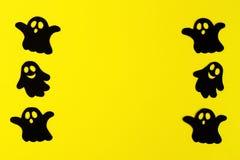 Capítulo de fantasmas de papel negros en un fondo amarillo Decoraciones del día de fiesta para Halloween con el espacio de la cop imagen de archivo libre de regalías
