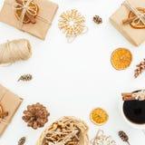 Capítulo de la decoración de la Navidad o del Año Nuevo, caja de regalo de papel, taza de café y conos del pino en el fondo blanc Imagen de archivo libre de regalías