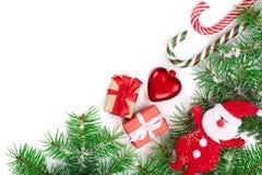 Capítulo de la Navidad de la rama de árbol de abeto con los bastones de caramelo y de la nieve aislada en el fondo blanco con el  Imagenes de archivo